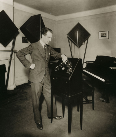 Lev Termen standing infront of custom theremin in an RCA Theremin cabinet with five ca. 1926 - 28 National